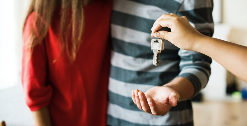 couple getting keys from realtor to new home