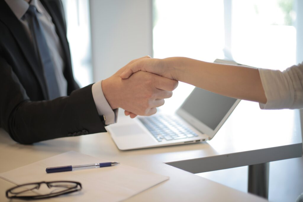 Domain broker and a seller shaking hands following a domain acquisition