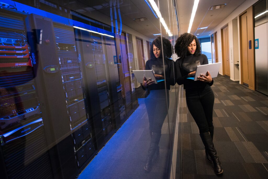 Woman leaning on a glass wall between her and domain servers.
