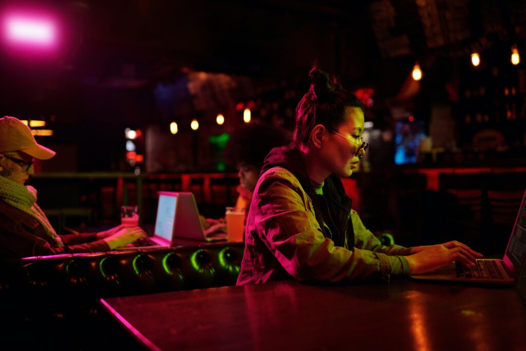 Woman in a dark restaurant reviewing domain security on her laptop.