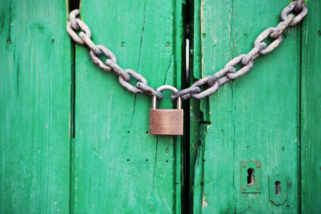 Padlock and chain securing a green wooden door.