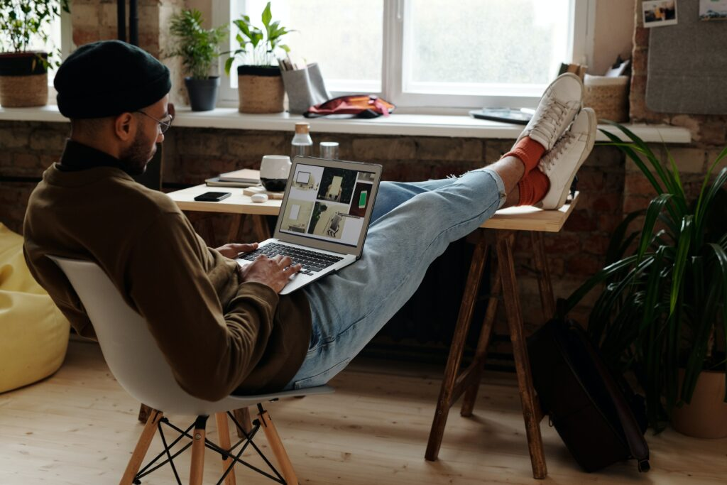 Man reclined in a chair with feet up on a wooden desk